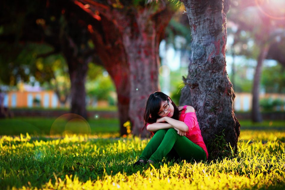 girl with hairloss sitting under a tree