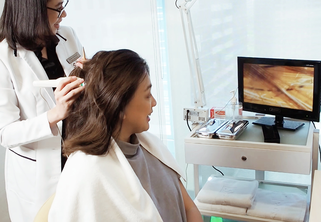 Trichologist gives a patient a hair and scalp analysis