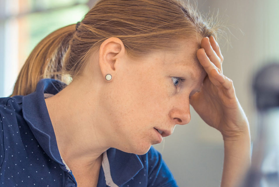 a visibly stressed woman holding her head
