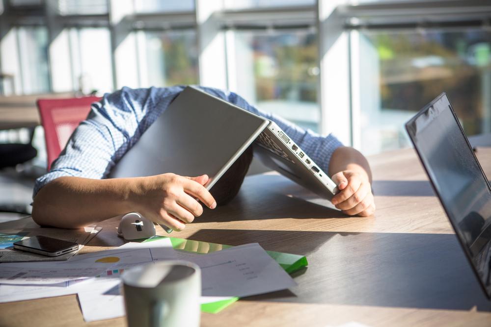 stressed man hides under laptop