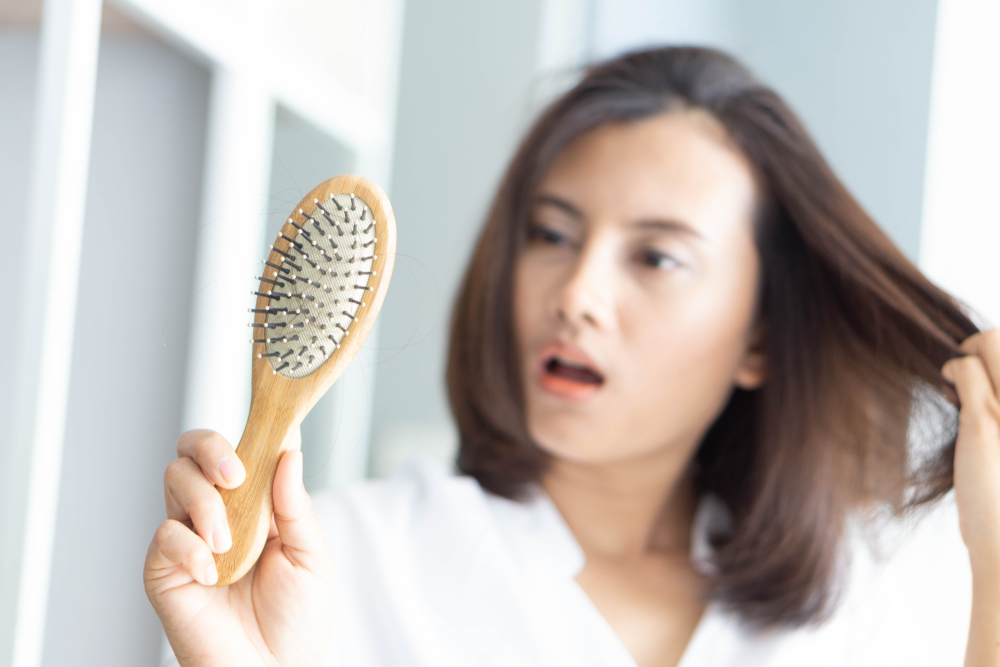 woman looks shocked at how much hair is stuck to her brush