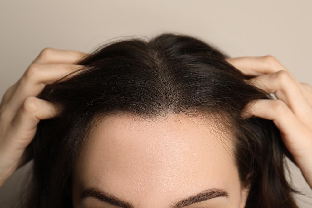 woman examining her hair