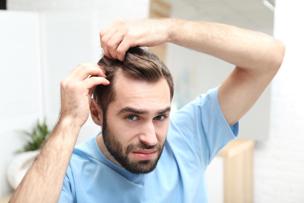 man trying to style thinning hair