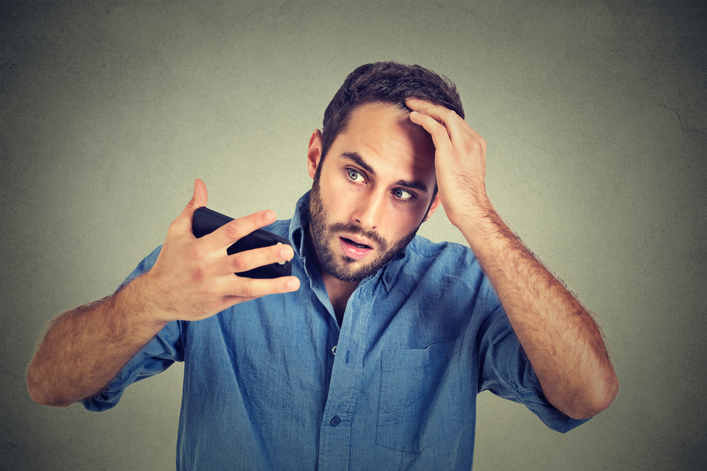 man worried about his hair while looking at photos